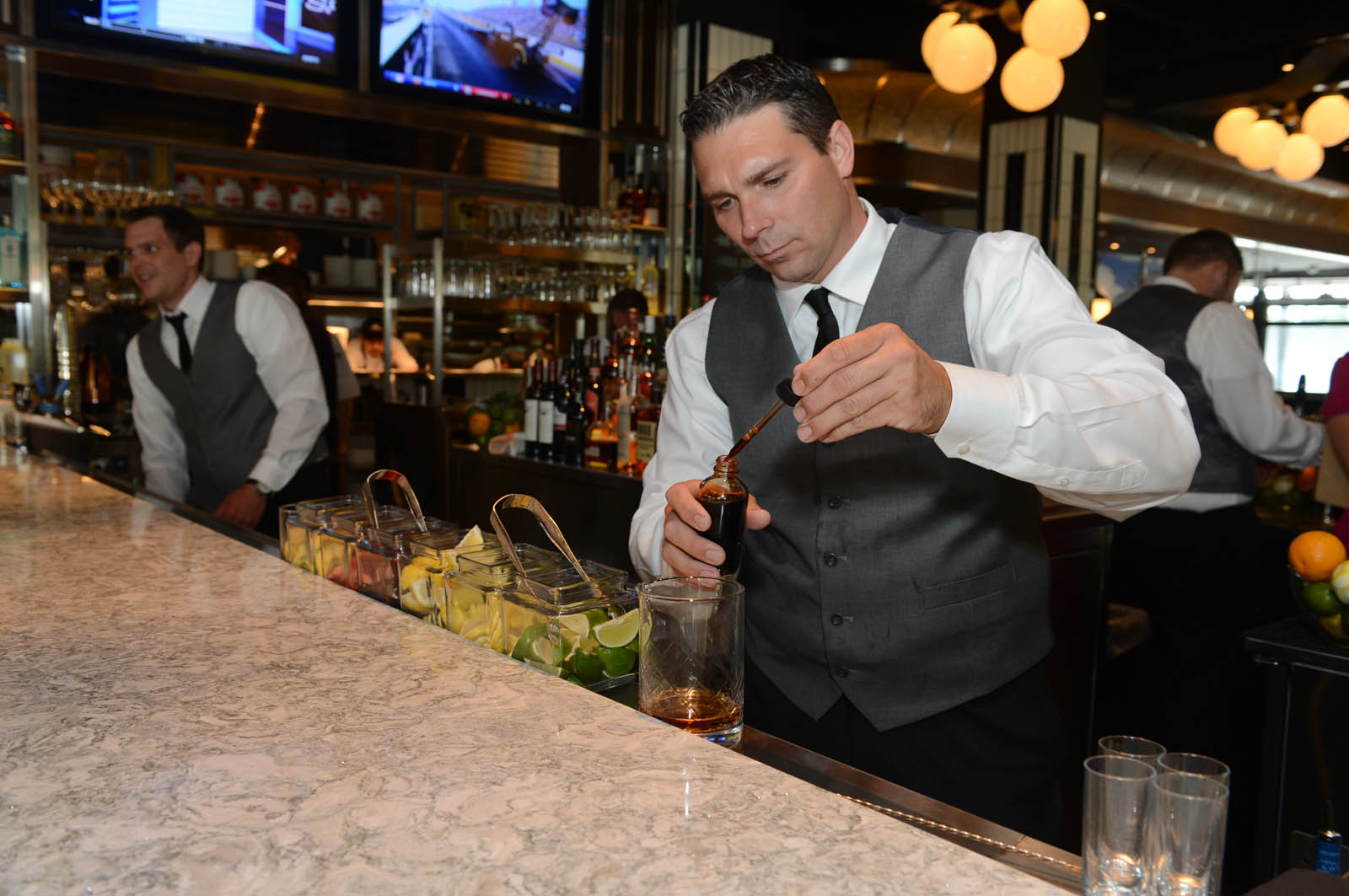 A bartender making a drink behind the bar