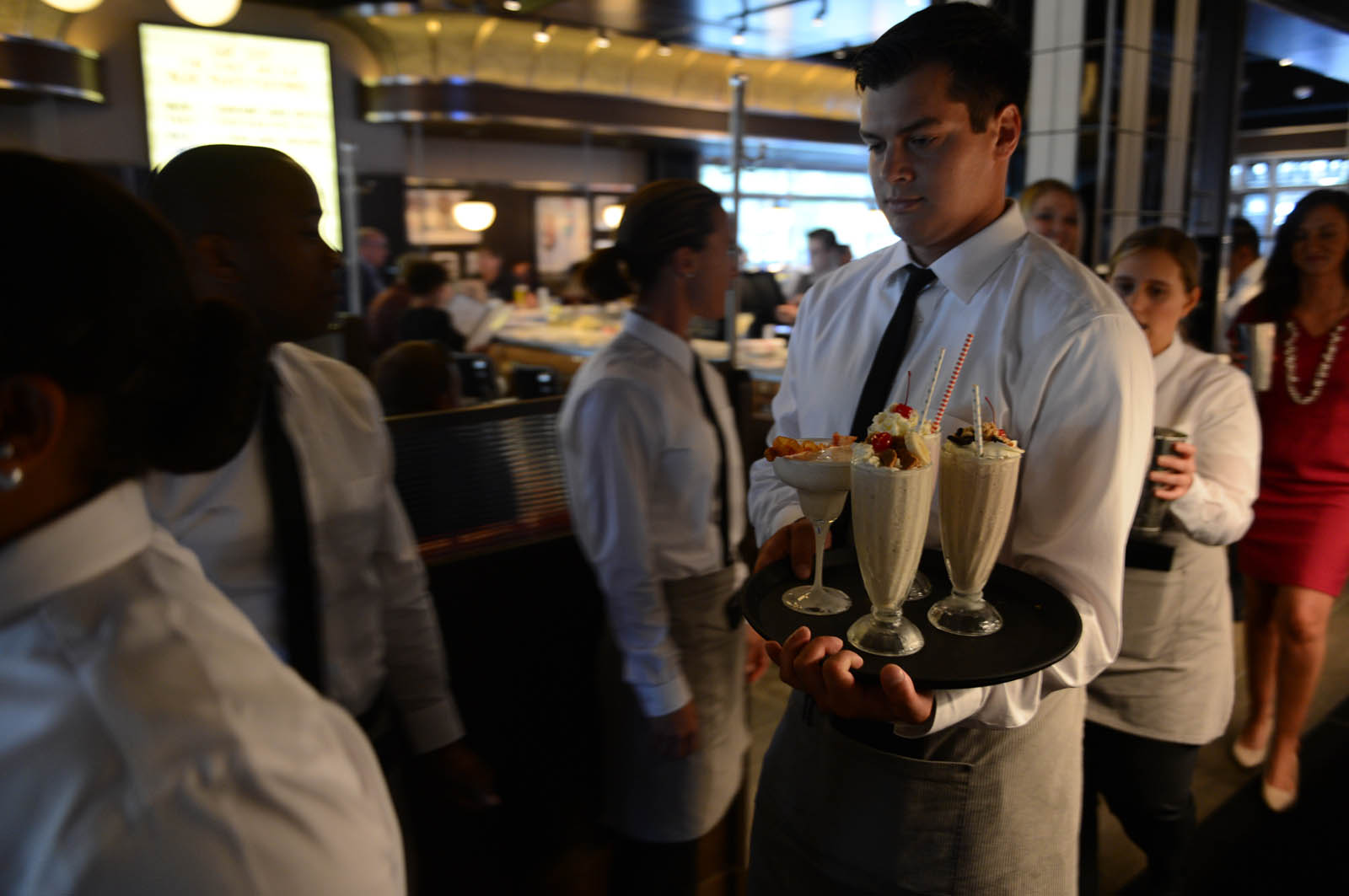 A server carrying a tray of milkshakes